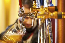 picture of tapping  - Pouring beer to a glass in a restaurant - JPG