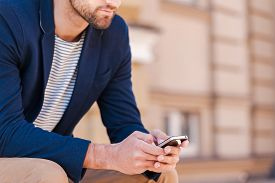 picture of sitting a bench  - Cropped image of handsome young man in smart jacket typing something on mobile phone while sitting on the bench outdoors - JPG