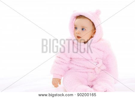 Portrait Of Sweet Baby In Soft Overalls Looking Away On A White Background