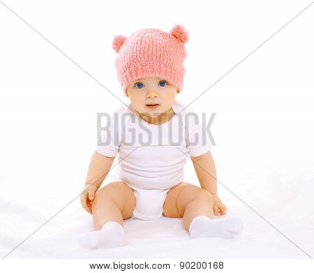 Portrait Of Sweet Baby Sitting In The Pink Knitted Hat