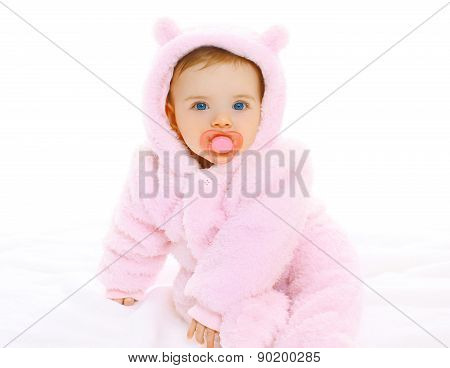 Portrait Of Sweet Baby With Pacifier In Soft Overalls On A White Background