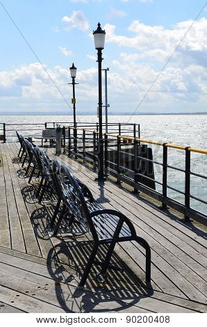 row of iron bench's on a Victorian pleasure pier in England