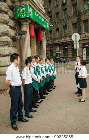Waiters Standing In Line In Front Of A Restaurant In Shanghai, China