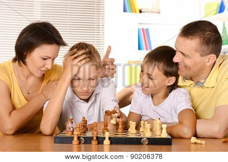 family playing chess sitting at table