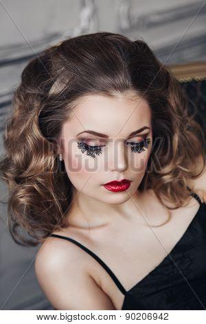 beautiful girl dark hair with unusual eyelashes in a black dress