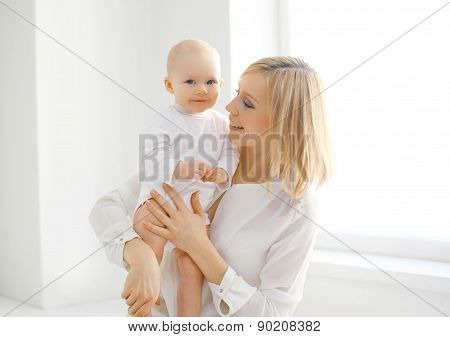 Family Portrait Of Mother And Baby Together At Home In White Room Near Window