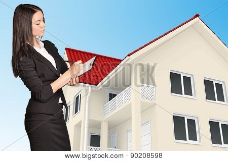 Office girl holding clip board standing on background of the house