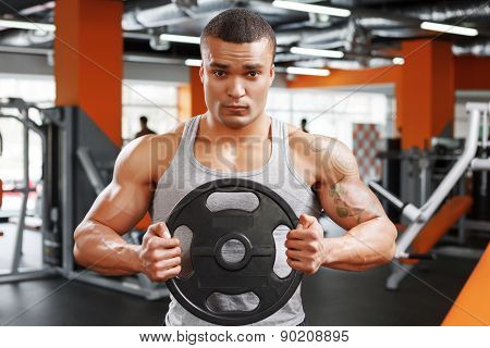 Powerlifter with weight disk in his hands