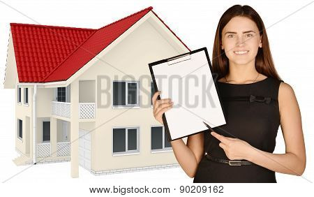 Office girl standing on background of country house, and indicates ballpoint pen in the clipboard