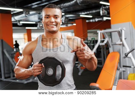 Weightlifter pointing on weight disk