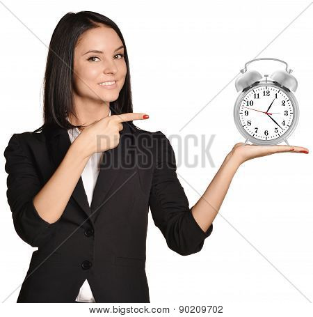 Woman standing and holding alarm clock on pointing at it