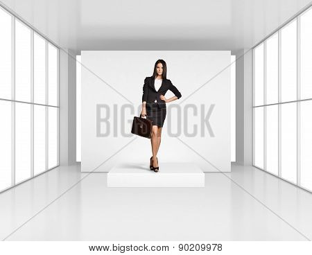 Young girl with leather briefcase standing on the podium in bright room