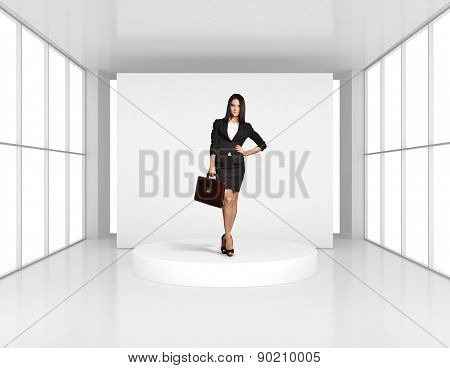 Business woman with leather briefcase standing on the podium in bright room