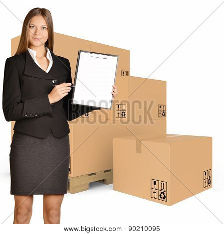 Woman standing with cardboard boxes on pallet and showing in clipboard