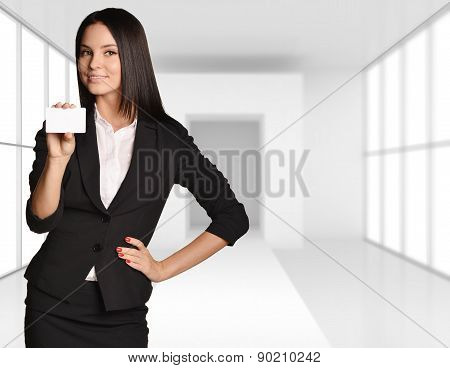 Young girl stands on the background of bright interior room and holding a blank business card