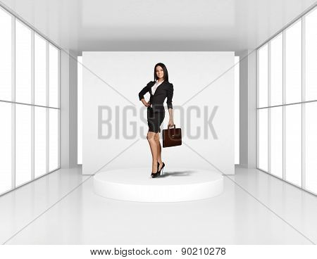 Girl stands on a round podium in an empty room light