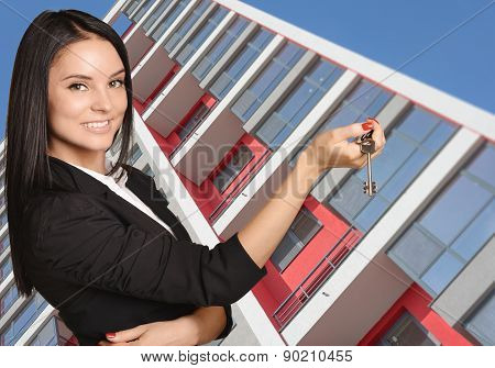 Successful Woman standing on background of building and is holding keys from apartment