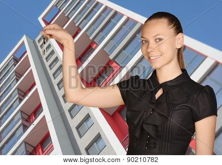 Young girl standing on background of building and is holding keys