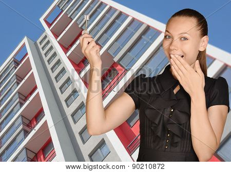 Successful girl standing on background of building and is holding keys