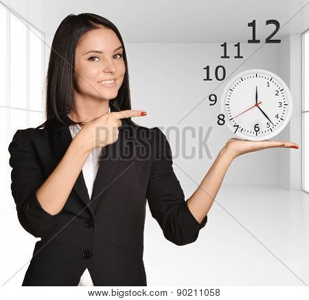 Office girl standing on background of light interior and holding clock numbers flying off