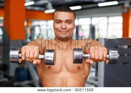 Man holding dumbbells in front of his chest.