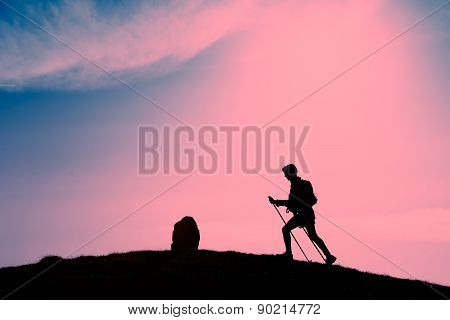 Silhouette Of Girl That Makes Trekking In A Pink Sunset