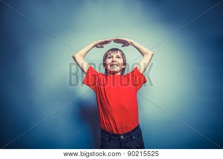 European-looking boy of ten years hands above  his head, a  gest