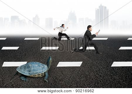 Two Businessmen Running With Turtle On Asphalt Road