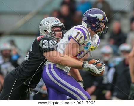 INNSBRUCK, AUSTRIA - MAY 3, 2014: TE Manuel Thaller (#11 Vikings) is tackled by DL Philipp Margreiter (#36 Raiders).