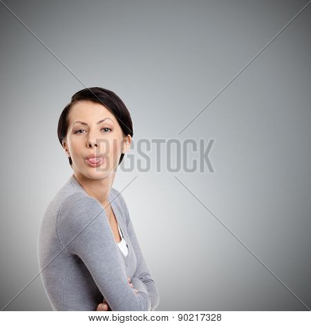 Young pretty woman sticks out tongue, isolated on grey