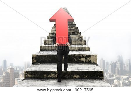 Businessman Carrying Red Arrow Sign On Old Stairs With Cityscape