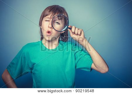 European-looking boy  of ten  years holding a magnifying glass,