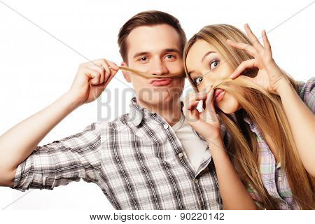 people, friendship, love and leisure concept - beautiful young loving couple making fake moustache from hair while standing isolated on white.