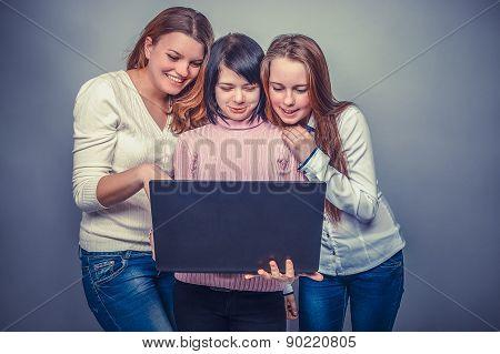 Three girls European  appearance  girlfriend looking at computer