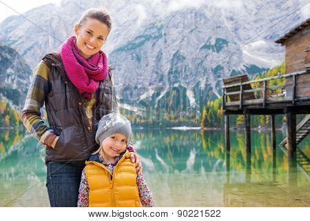 Smiling Mother And Blonde Daughter Posing At Lake Bries