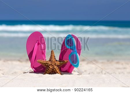 Pink Flip Flops, Swimming Glasses And Starfish On White Sandy Beach