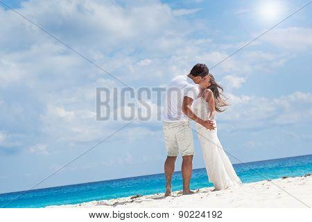 Newlyweds Kissing On White Sandy Beach