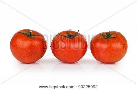 Three Tomatoes In Water Droplets On White