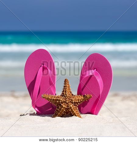 Pink Flip Flops And Starfish On White Sandy Beach