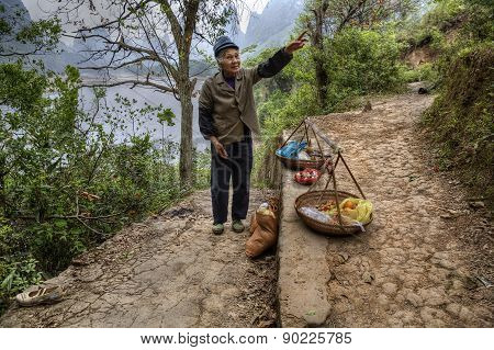 Elderly Asian Peasant Farmer Sells Food On The Tourist Trail.