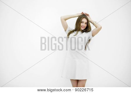 Beautiful young sexy woman in a light gray dress posing against a white wall