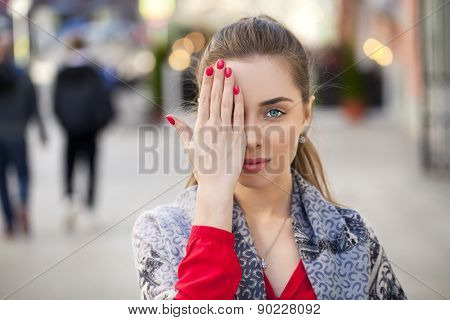 Young beautiful woman closes her eyes with his hand on a background of the street