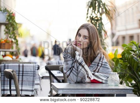 Portrait of a beautiful young woman sitting in a cafe on the street