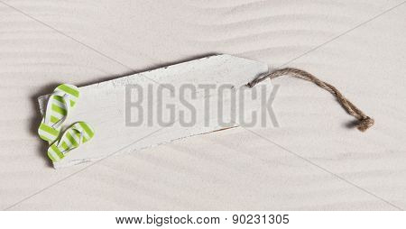 Summer background with a wooden sign and bathing shoes in the sand.
