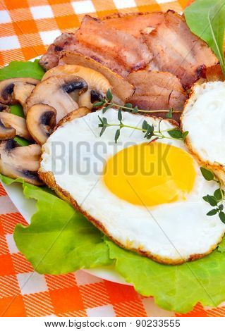 Bacon With Sunny Side Up Eggs Served With Toasts On A Orange Napkin