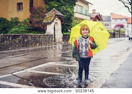 Cute little boy with umbrella playing in the puddle