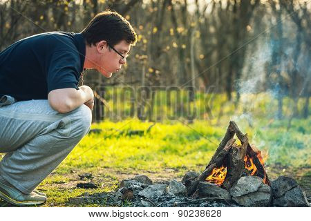 Man And Bonfire In Spring Forest. Coals Of Fire. Sunset