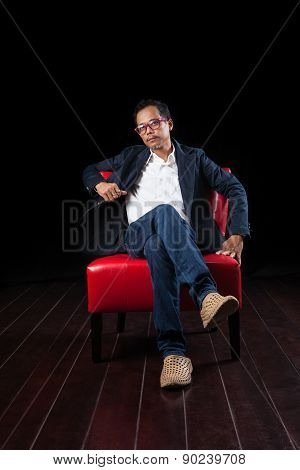 Portrait Of 45 Years Old Asian Man Sitting On Red Sofa Against Black Background