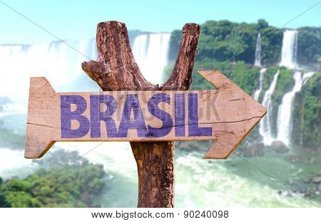 Brazil (in Portuguese) wooden sign with Igua�?�§u Falls on background