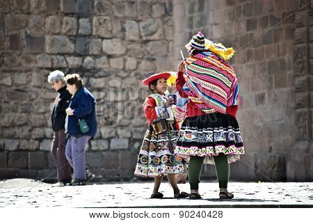 Quechua Indians Break From Posing With Tourists